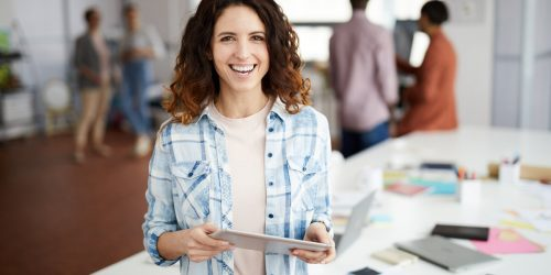 Waist up portrait of cheerful contemporary woman smiling at camera while posing in office, copy space